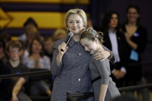 Democratic presidential candidate Hillary Clinton gets a hug from fifth-grader Hannah Tandy during a town hall meeting at Keota High School in Keota, Iowa. (AP Photo/Charlie Neibergall)